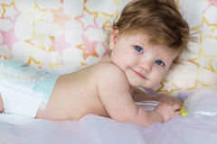 Pretty little baby lies and smiles. Stock Photography