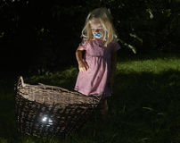 Pretty little blond child girl in the woods with a basket Stock Image