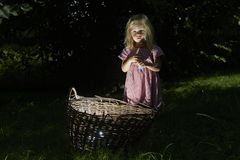 Pretty little blond child girl in the woods with a basket Royalty Free Stock Photos