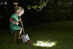 Child girl have unearthed a treasure in the grass Royalty Free Stock Photo
