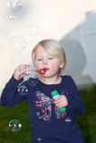Pretty little blond girl blowing soap bubbles Royalty Free Stock Image
