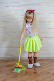 Pretty little blond girl cleaning the house Royalty Free Stock Photography
