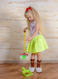 Pretty little blond girl cleaning the house Royalty Free Stock Photos