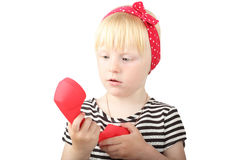 Pretty  little blond girl looking at a a red  retro phone on a w Stock Photo