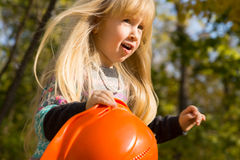 Pretty little blond girl playing with a hardhat Stock Photo