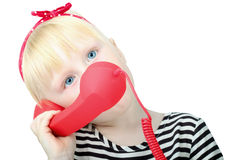 Pretty  little blond girl with a red  retro phone, isolated on a Stock Image
