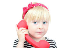 Pretty  little blond girl with a red  retro phone on a white bac Stock Images