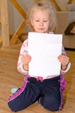Pretty little blond girl sitting reading a letter Stock Photography