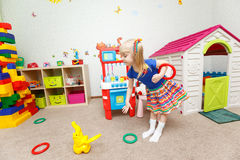 Pretty little blond girl throwing toy rings in kindergarten Stock Image