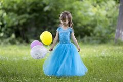 Pretty little blond long-haired girl in nice long blue evening d. Ress holds colorful balloons standing in blooming field on blurred green trees background on royalty free stock images