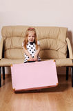 Pretty little blonde girl drags big pink suitcase near sofa Royalty Free Stock Image