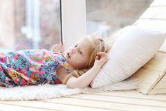 Pretty little blonde girl lies on white pillow near window Stock Photos