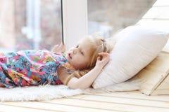 Pretty little blonde girl lies on white pillow near window Stock Photos