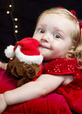 Pretty little blonde girl with red clothes and toy Stock Image