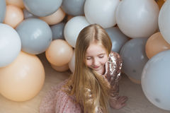 Pretty little blonde girl sits on a floor with balloons Royalty Free Stock Photography