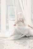 Pretty little blonde girl sits near big window and hides Royalty Free Stock Image