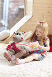 Pretty little blonde girl sits near soft toy on carpet. In cozy room and reads book Royalty Free Stock Photography