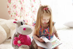 Pretty little blonde girl sits near soft toy on carpet and reads Stock Photography