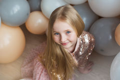 Pretty little blonde girl sits and smiles on floor with balloons Royalty Free Stock Photo