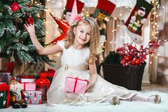 Pretty little blonde girl smiling with a flower hair clip and beige dress with present decorates a Christmas tree The concept of C. Hristmas royalty free stock images