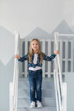 Pretty little blonde girl stands on stairs at home Stock Photo