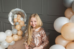 Pretty little blonde girl in a studio with on a balloons Stock Images