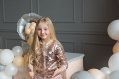 Pretty little blonde girl in a studio decorated a colorful balloons Royalty Free Stock Photos