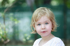 Pretty little blue eyed blond girl staring intently at the camera Stock Photos