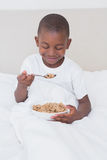 Pretty little boy eating cereals in bed Royalty Free Stock Photo