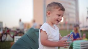 Pretty little boy having fun at the park in summer day, holding a glass with straws and laughing. stock video