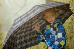 Pretty little boy posing under umbrella, close-up Royalty Free Stock Image