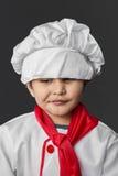 Pretty little boy preparing healthy food on kitchen over grey ba Stock Image