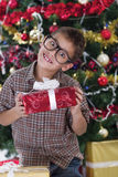 Pretty little boy smiling with present near the Christmas tree Royalty Free Stock Images