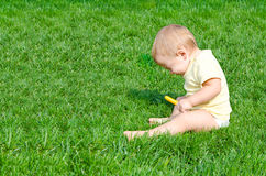 А pretty little boy sneezes. Sitting on a grass Royalty Free Stock Photography