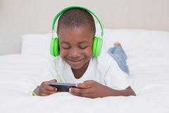 Pretty little boy using smartphone and listening music in bed Stock Photography