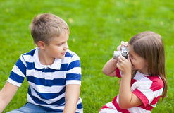 Pretty little brother and sister playing with a camera in summer Stock Images