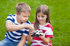 Pretty little brother and sister playing with a camera in summer Stock Photography
