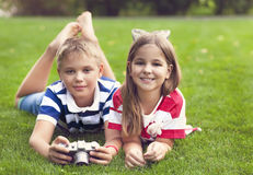 Pretty little brother and sister playing with a camera in summer Royalty Free Stock Images