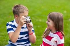 Pretty little brother and sister playing with a camera in summer. Young photographers. Pretty little brother and sister playing with a camera in summer park Stock Image