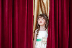 Pretty little brunette posing on curtain backdrop Royalty Free Stock Images