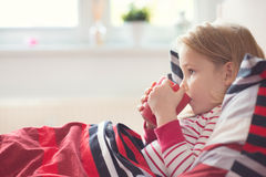 Pretty little child girl laying in bed and drink tea Royalty Free Stock Photography