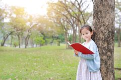 Pretty little child girl reading book in park outdoor standing lean against tree trunk in summer garden.  stock photography