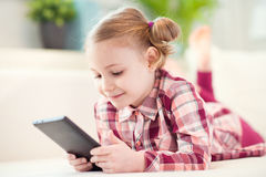 Pretty little child girl using a digital tablet Stock Photos
