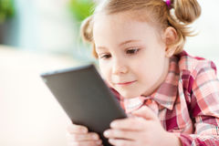 Pretty little child girl using a digital tablet Royalty Free Stock Photos