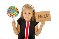 Pretty little child holding lollipop and help sign in children sugar excess  Royalty Free Stock Photos