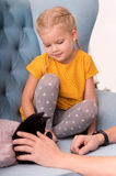 Pretty little child looking at a black kitten Royalty Free Stock Photo