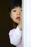 Pretty little child stands behind a door Stock Image