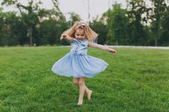 Pretty little cute child baby girl in denim dress circling around and have fun on green grass lawn in park. Mother. Little kid daughter. Mother`s Day, love royalty free stock photography