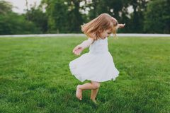 Pretty little cute child baby girl in light dress circling around and have fun on green grass lawn in park. Mother. Little kid daughter. Mother`s Day, love royalty free stock image
