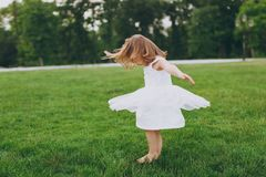 Pretty little cute child baby girl in light dress circling around and have fun on green grass lawn in park. Mother. Little kid daughter. Mother`s Day, love royalty free stock images